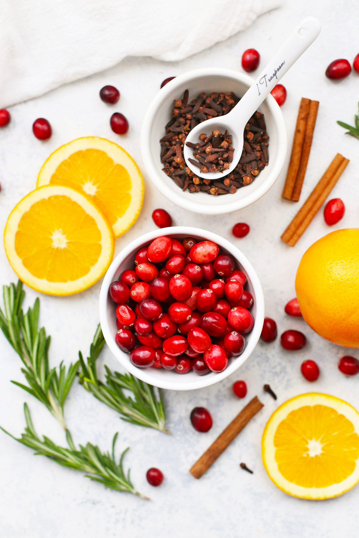 Ingredients for Stovetop Christmas Potpourri - Cranberries, oranges, rosemary, cinnamon sticks, and whole cloves.