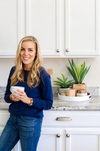 Emily from OneLovelyLife.com in her white kitchen.