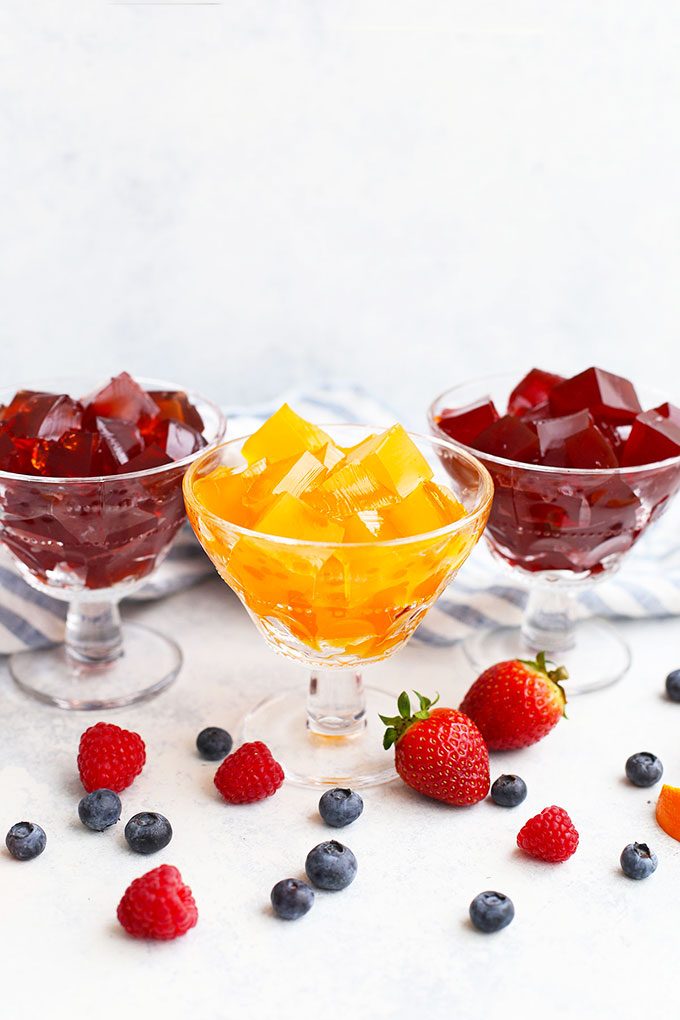 Three dessert bowls of healthy homemade Jello with fresh fruit.