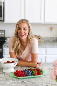 Emily from One Lovely Life in a pink v neck tee at her counter with a jade milk glass tray of fresh fruit.