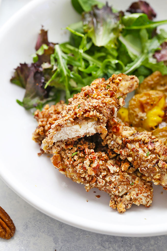 Close up view of Pecan Crusted Chicken Tenders stacked on top of one another from One Lovely Life.
