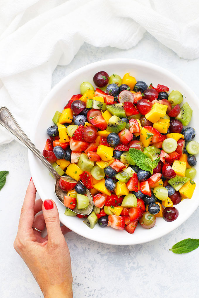 Overhead view of a bowl of Rainbow Fruit Salad with Citrus Mint Dressing from One Lovely Life with mint leaves scattered on a white background.