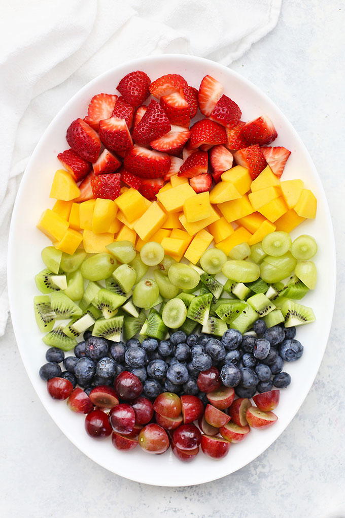 Platter of fruit arranged in rainbow order for Rainbow Fruit Salad with Citrus Mint Dressing from One Lovely Life
