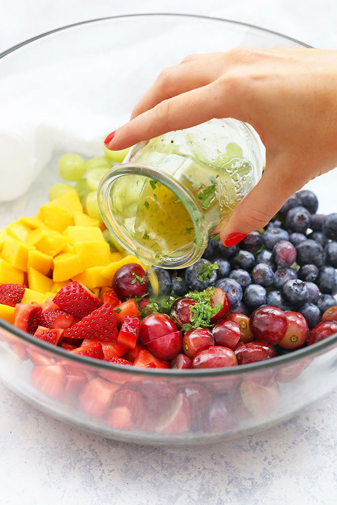 Citrus Mint Dressing Being Poured over a Bowl of Rainbow Fruit Salad by One Lovely Life