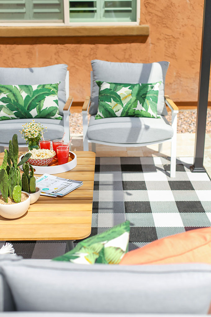 Elena Cera Gray Lounge Chairs from Article styled with banana leaf lumbar pillows and a black and white gingham outdoor rug