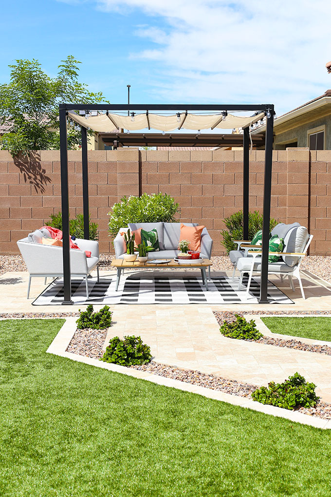 Outdoor living area with pergola, grey outdoor sofas, grey outdoor chairs, black and white gingham rug and pink and green accessories.
