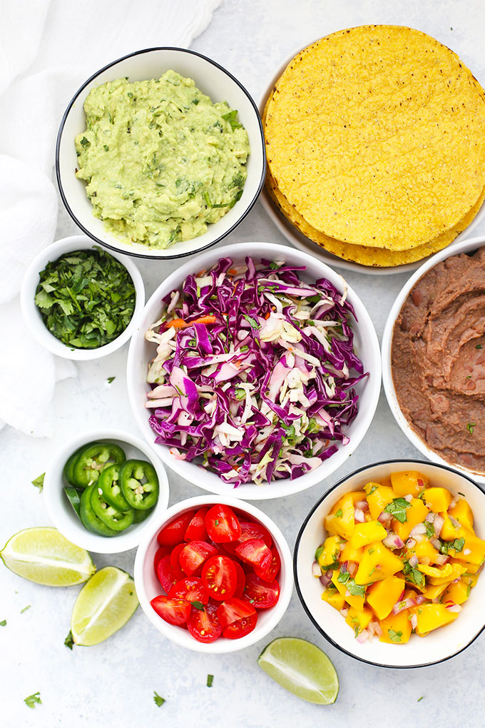 Ingredients and toppings for Black Bean Tostadas - Corn tostada shells, refried black beans, fresh mango salsa, cilantro slaw, diced tomatoes, jalapeños, and cilantro.