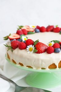Close up of Gluten Free Lemon Cake with Icing dripping down the sides. Topped with fresh berries and chamomile blossoms from One Lovely Life