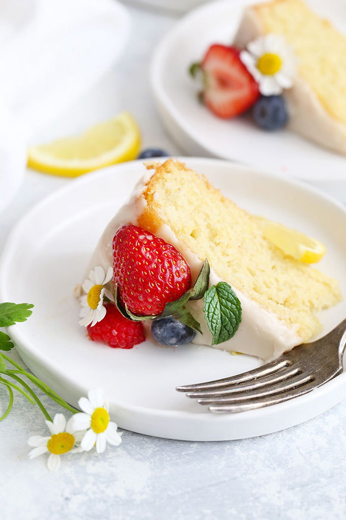 A slice of gluten free lemon cake with lemon icing and fresh berries from One Lovely Life