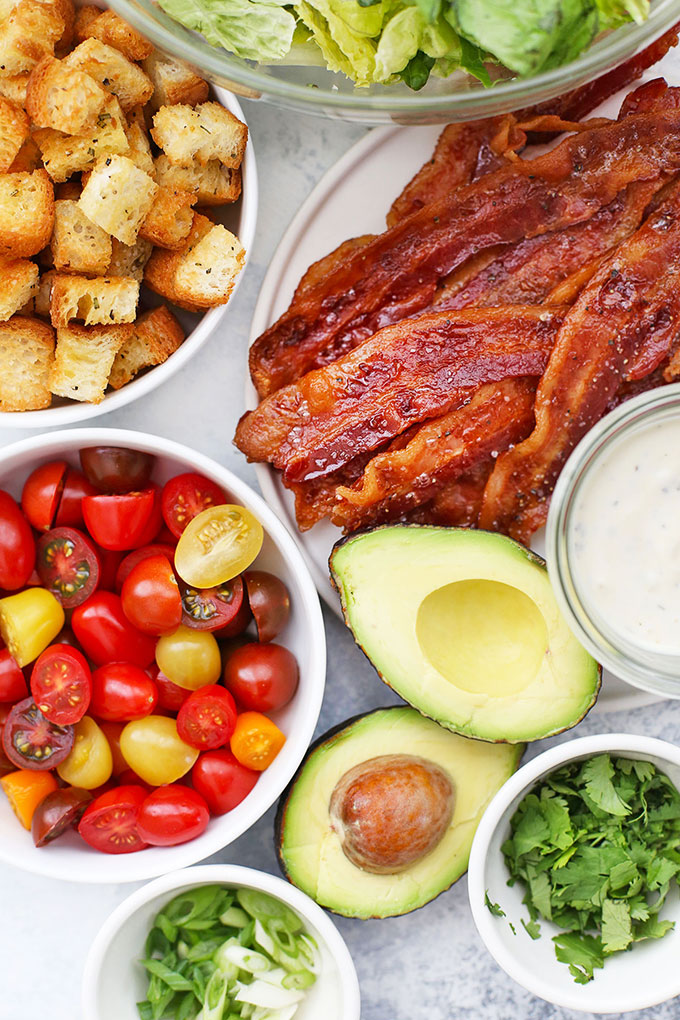 Ingredients for BLT Salad - Gluten free croutons, crispy bacon, tomatoes, avocado, fresh herbs, and ranch dressing