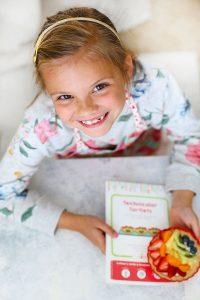 Little girl holding a Raddish Kids recipe card and Rainbow Fruit Tartlet