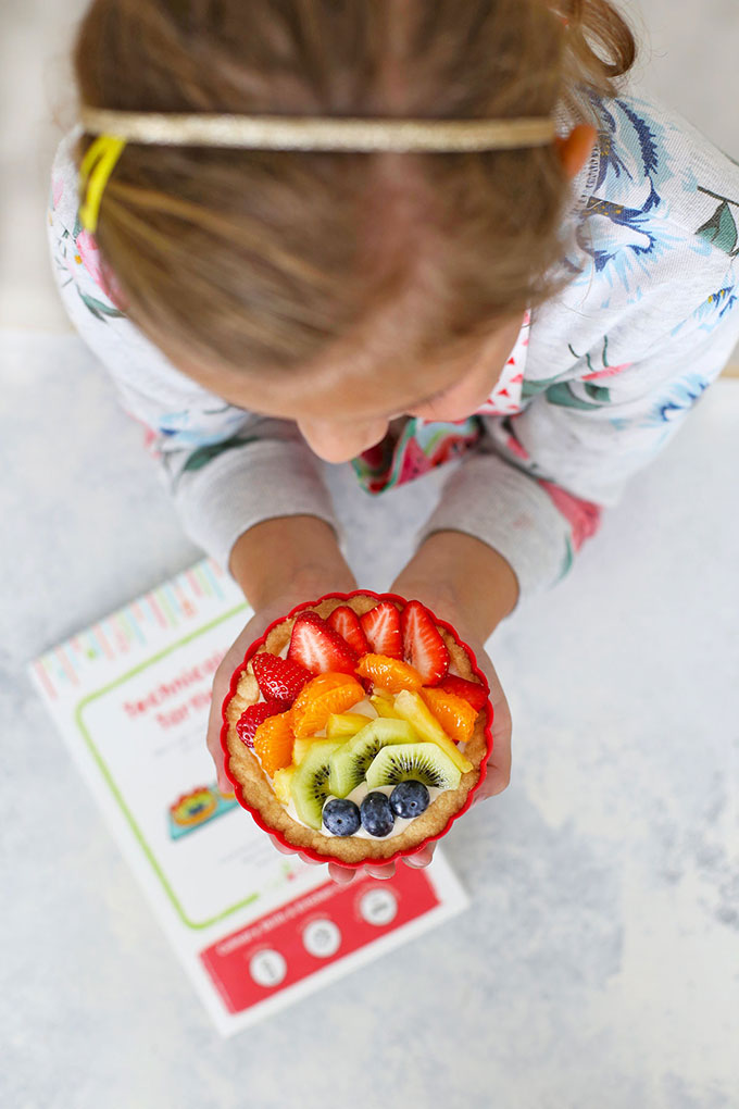Little girl holding a Raddish Kids Rainbow Fruit Tartlet
