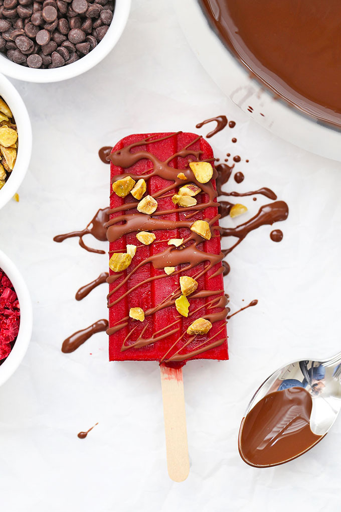 Healthy Raspberry Sorbet Popsicle Drizzled with Healthy Chocolate Shell and Chopped Pistachios