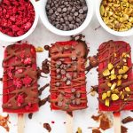 Paleo & Vegan Raspberry Sorbet Popsicles on a baking sheet, drizzled with chocolate shell and sprinkled with mini chocolate chips, chopped pistachios, and freeze dried raspberries