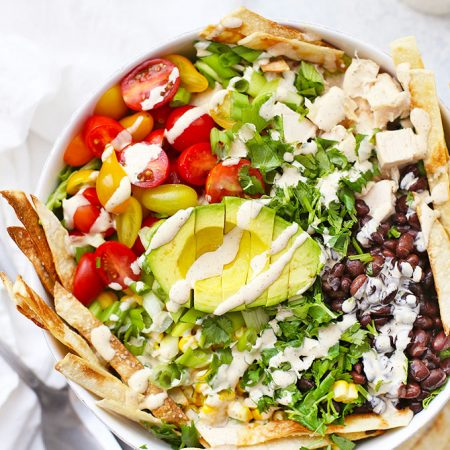 Southwest Chicken Salad drizzled with Southwest Ranch Dressing in a large white salad bowl.