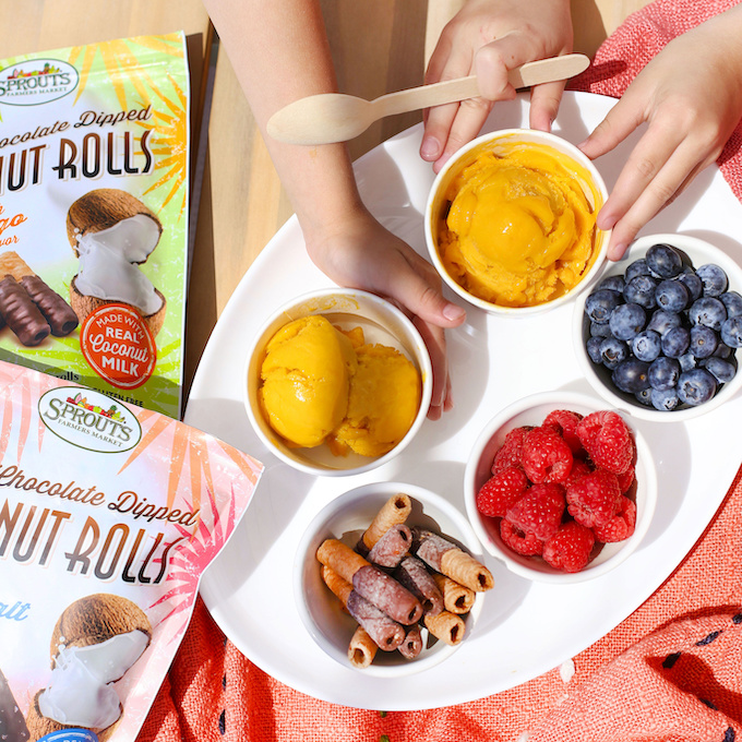 Overhead view of kids eating mango sorbet with blueberries, raspberries, and Sprouts coconut rolls for toppings.