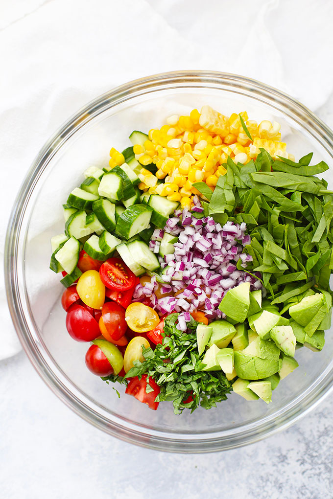 Clear glass bowl with ingredients for Farmers' Market Quinoa Salad - Sweet Corn, spinach, avocado, red onion, fresh basil, grape tomatoes, cucumber, and quinoa