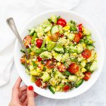 White bowl of Farmer's Market Quinoa Salad with sweet corn, avocado, cucumber, and tomatoes.