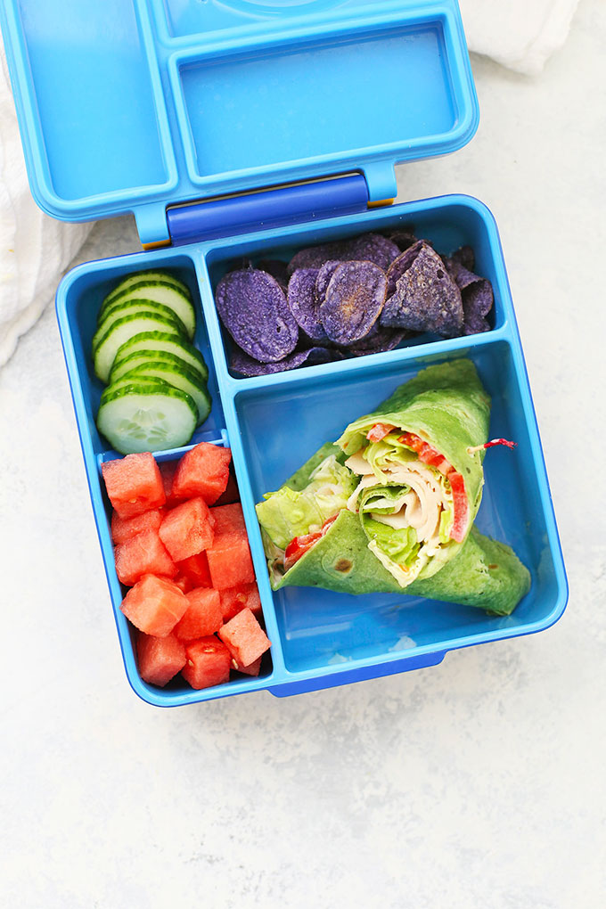 Gluten Free, Dairy Free Turkey Wrap Sandwich School Lunch with Purple Potato Chips, Diced Watermelon, and Sliced cucumbers from One Lovely Life