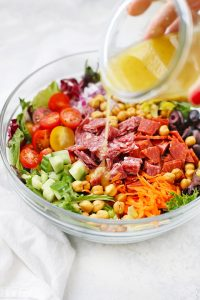 Pouring Italian Dressing on Italian Chopped Salad from One Lovely Life