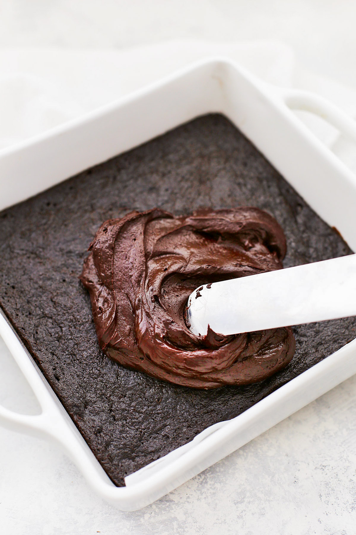 Front view of spatula spreading healthy chocolate frosting onto gluten free chocolate zucchini cake