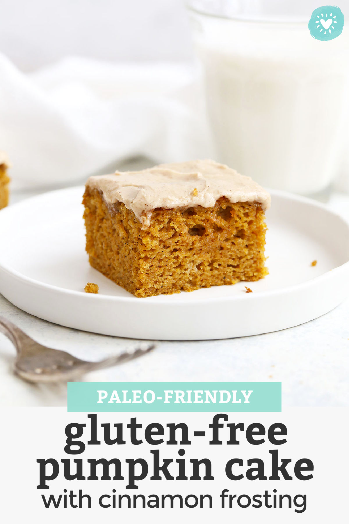 """Slice of gluten free pumpkin cake with cinnamon frosting on a white plate with text overlay that reads """"Paleo Friendly Gluten Free Pumpkin Cake with Cinnamon Frosting"""""""