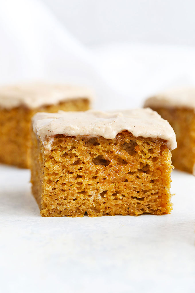 Slices of Gluten Free Pumpkin Cake with Cinnamon Frosting on a white background