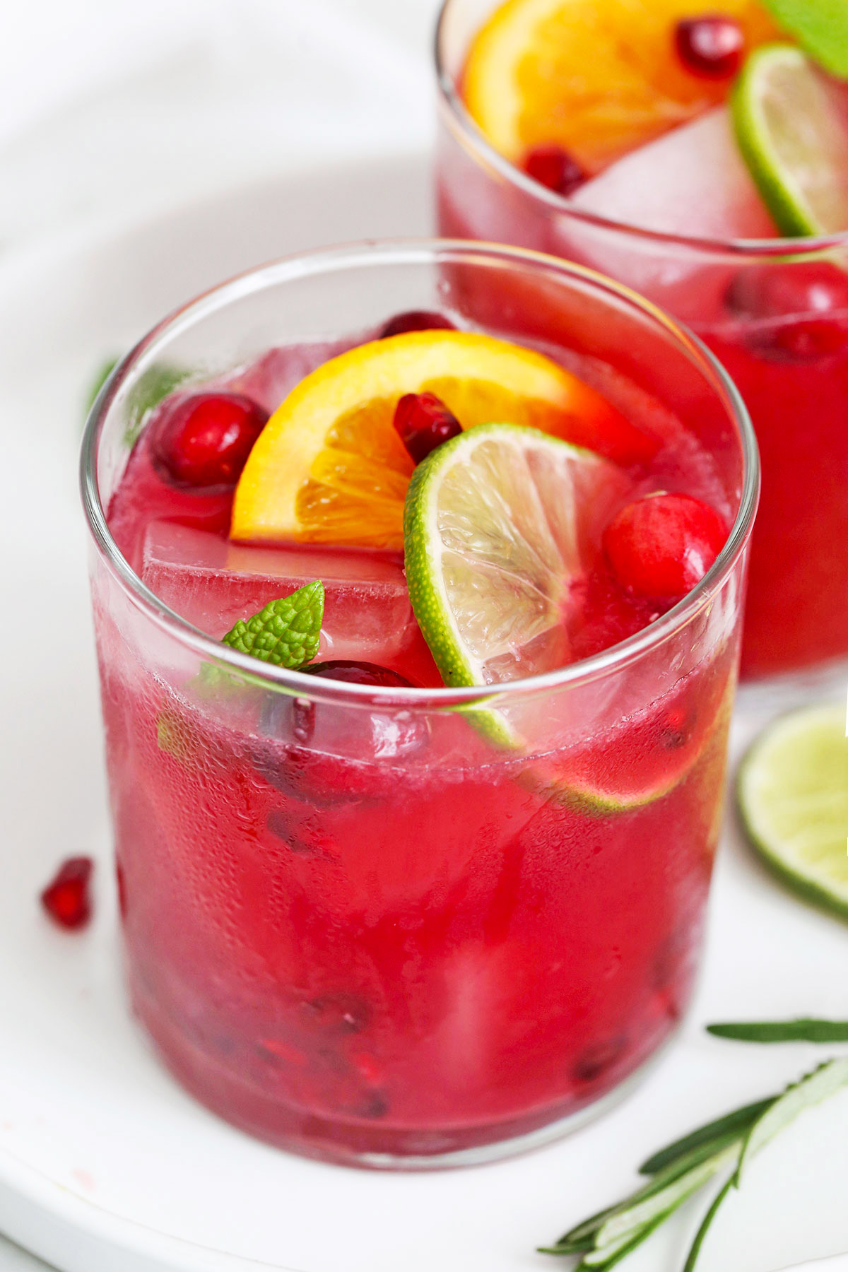 Close up view of Two Non-alcoholic sparkling citrus pomegranate mocktails on a white plate