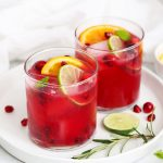 Two Non-alcoholic sparkling citrus pomegranate mocktails on a white plate