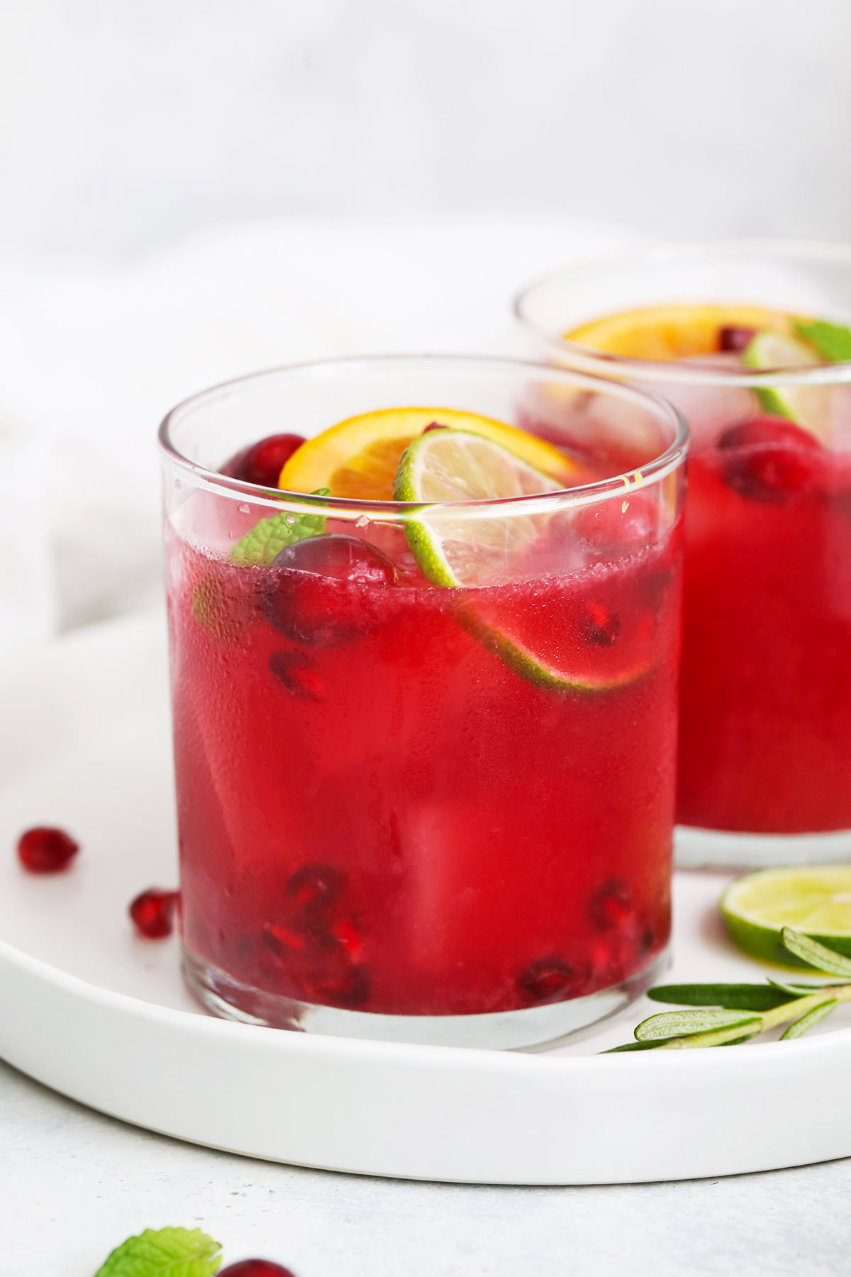 Front view of Two Non-alcoholic sparkling citrus pomegranate mocktails on a white plate