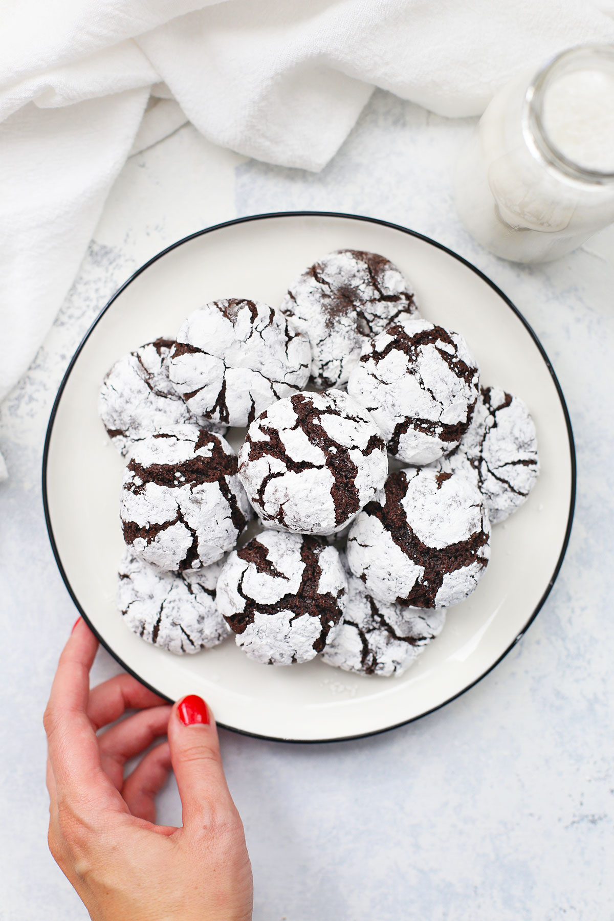 Overhead view of a plate of gluten-free chocolate crinkle cookies on a white background