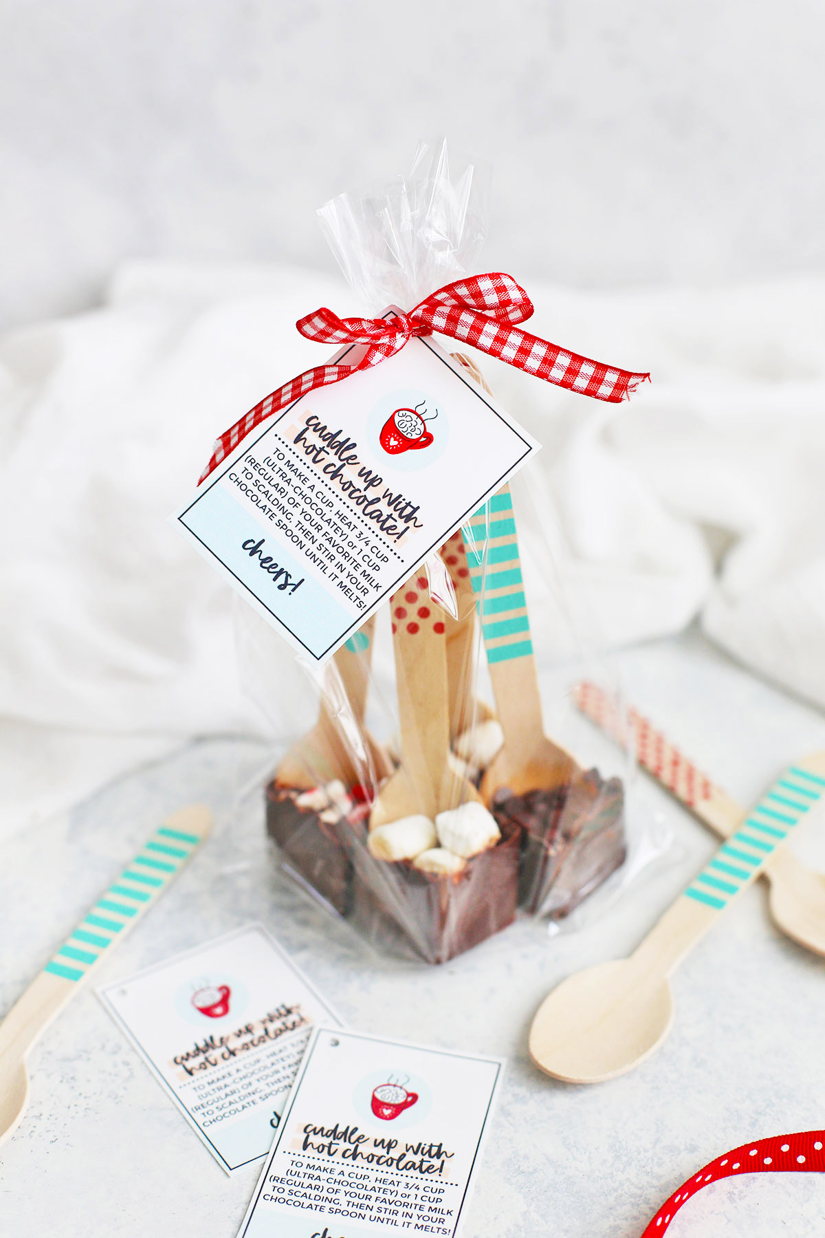 Four hot chocolate spoons wrapped in a clear treat bag with red ribbon and a free printable gift tag