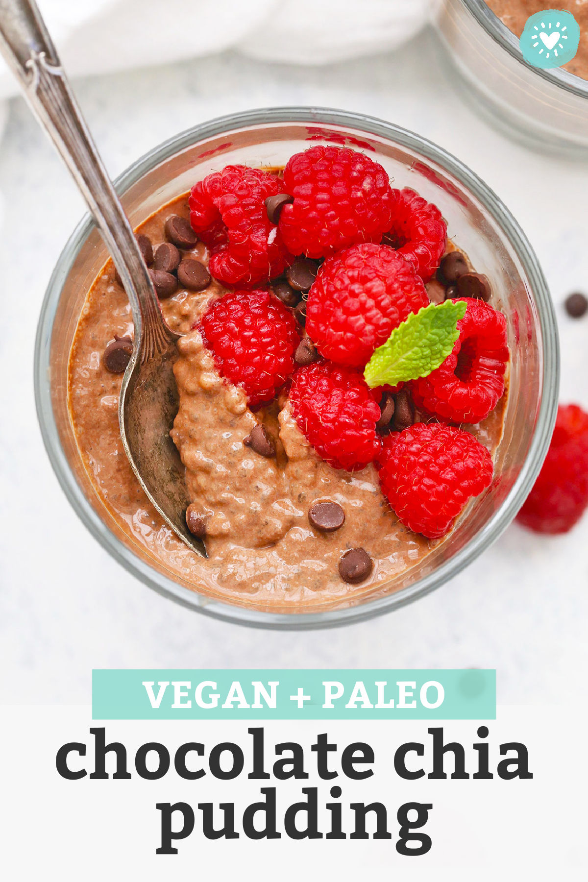 """Chocolate Chia Pudding in a glass dessert dish topped with raspberries with text overlay that reads """"Vegan + Paleo Chocolate Chia Pudding"""""""