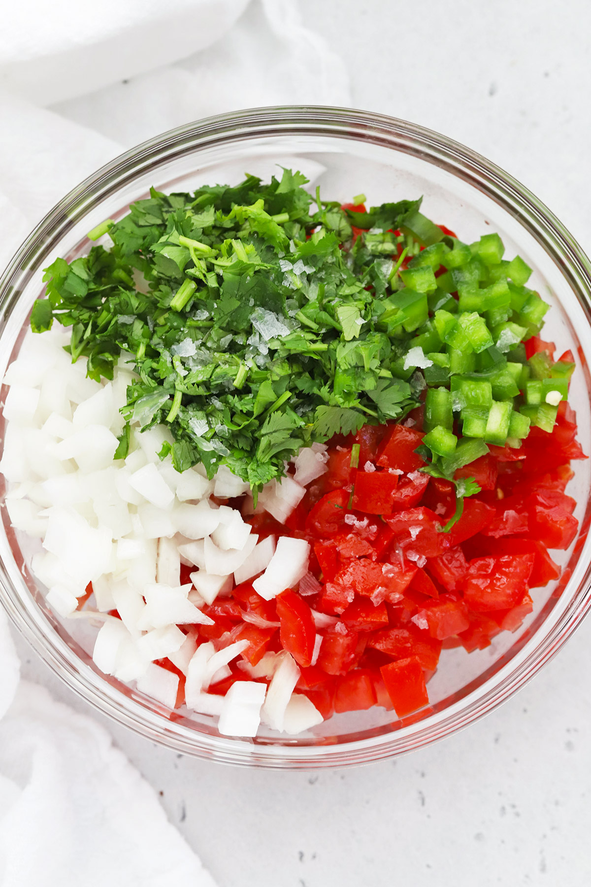 Overhead view of a bowl of pico de gallo ingredients ready to be mixed