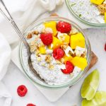 Overhead View of Jars of Mango Chia Pudding Topped with Raspberries, Granola, and Fresh Mango