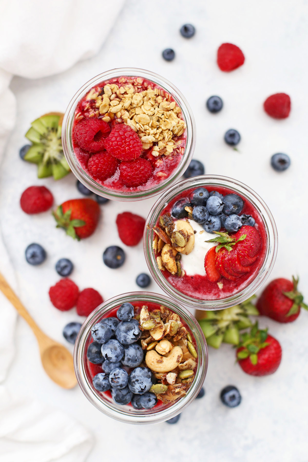 Jars of Paleo Granola Fruit and Yogurt Parfaits with fresh fruit scattered around the background.