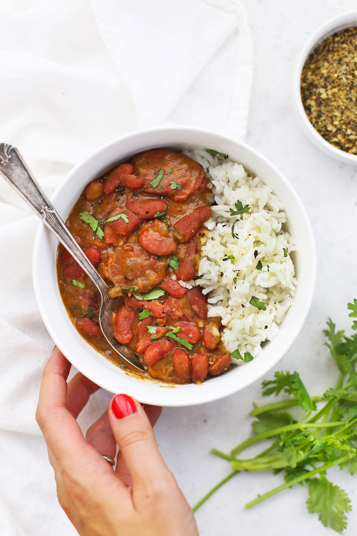 Serving Instant Pot Red Beans and Rice in a bowl garnished with fresh herbs