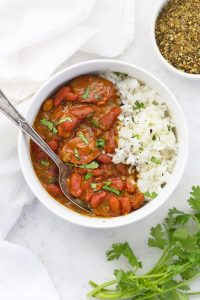Close overhead view of Instant Pot Red Beans and Rice in a bowl garnished with fresh herbs
