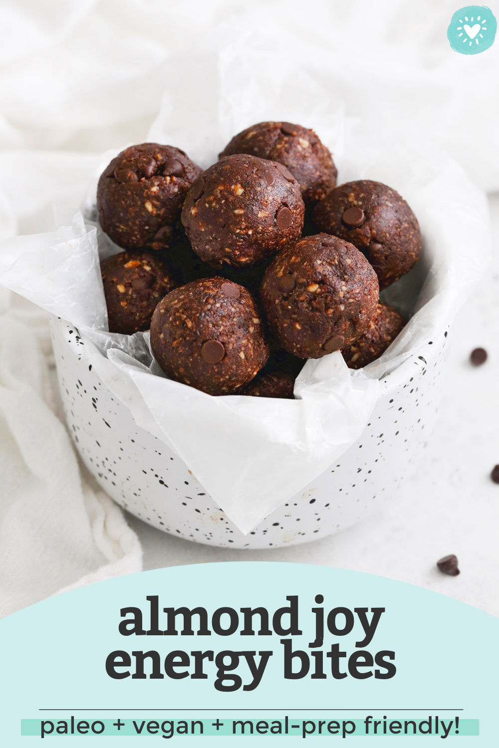 """Almond Joy Energy Bites in a white speckled bowl with a text overlay that reads """"almond joy energy bites. Vegan + paleo + meal-prep friendly"""""""