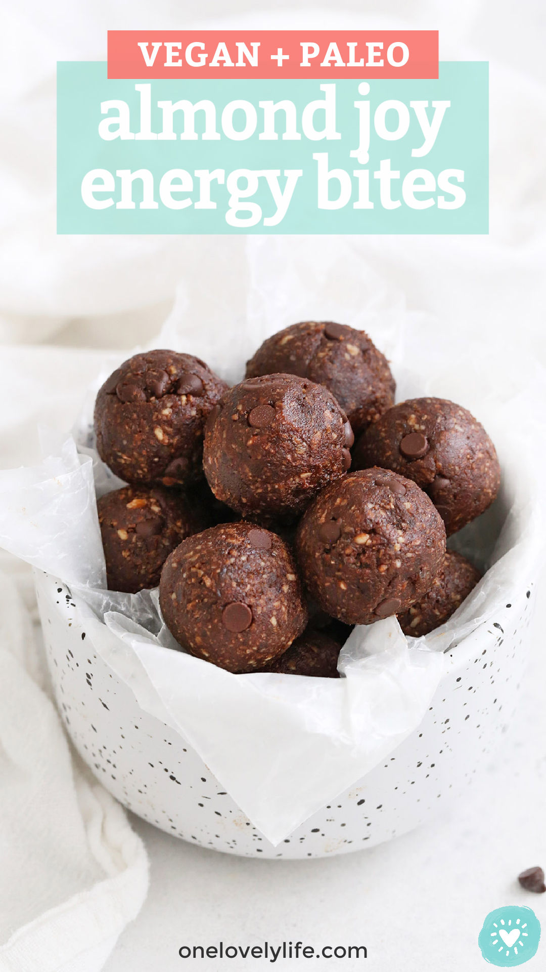 """Almond Joy Energy Bites in a white bowl with speckles with Text Overlay that reads """"vegan + paleo almond joy energy bites"""""""
