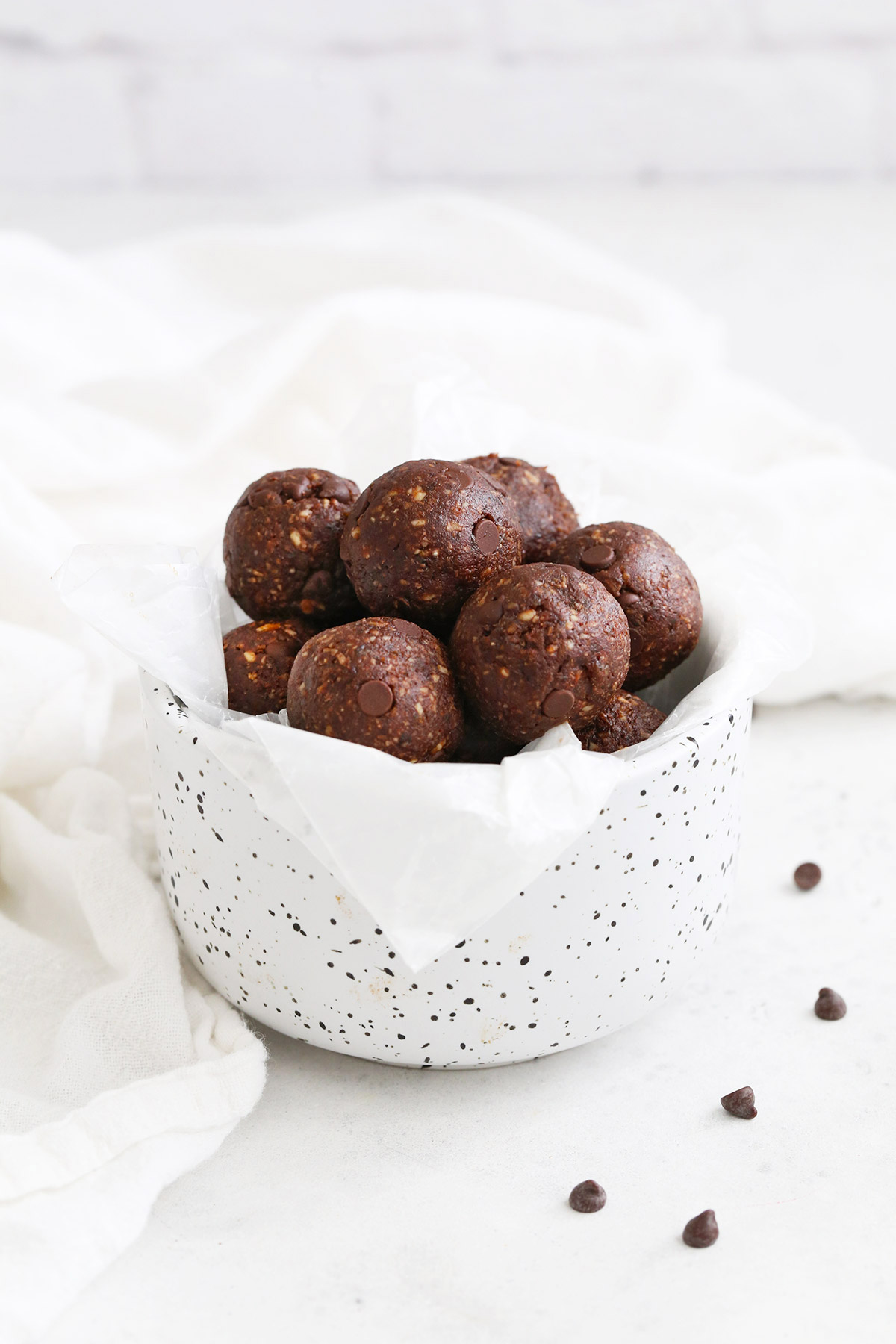 Front view of almond joy energy bites in a speckled white bowl.