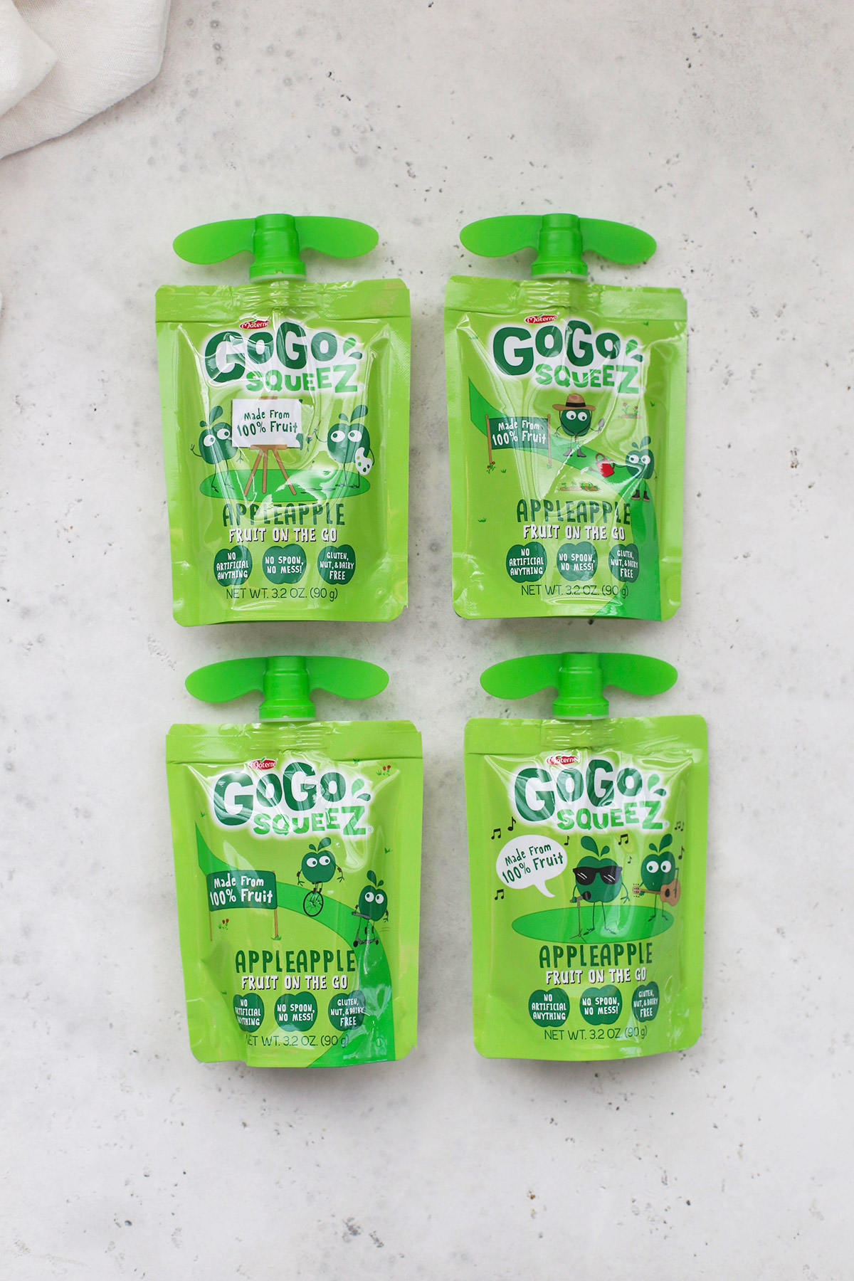 Four GoGoSqueez Applesauce pouches on a white background