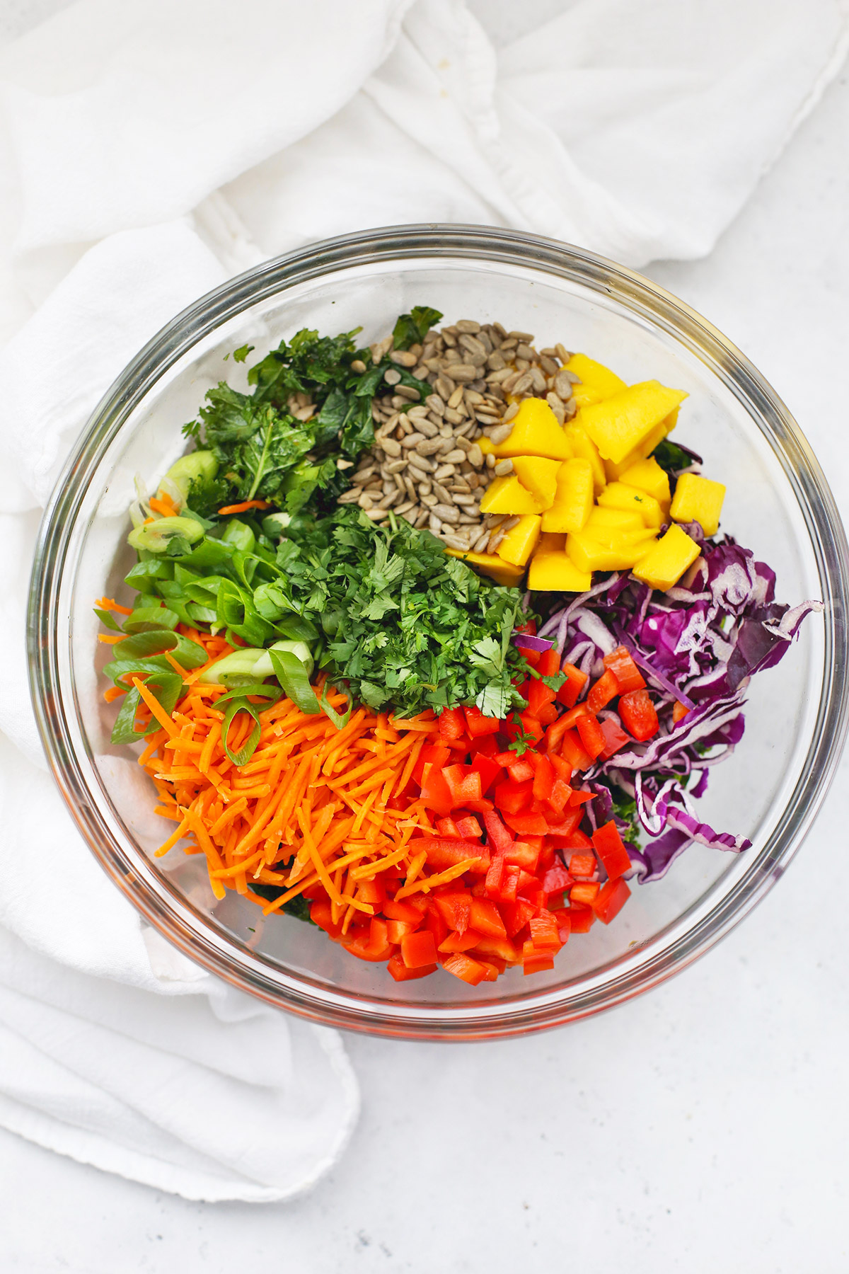 Glass bowl with ingredients for Asian Kale Crunch Salad