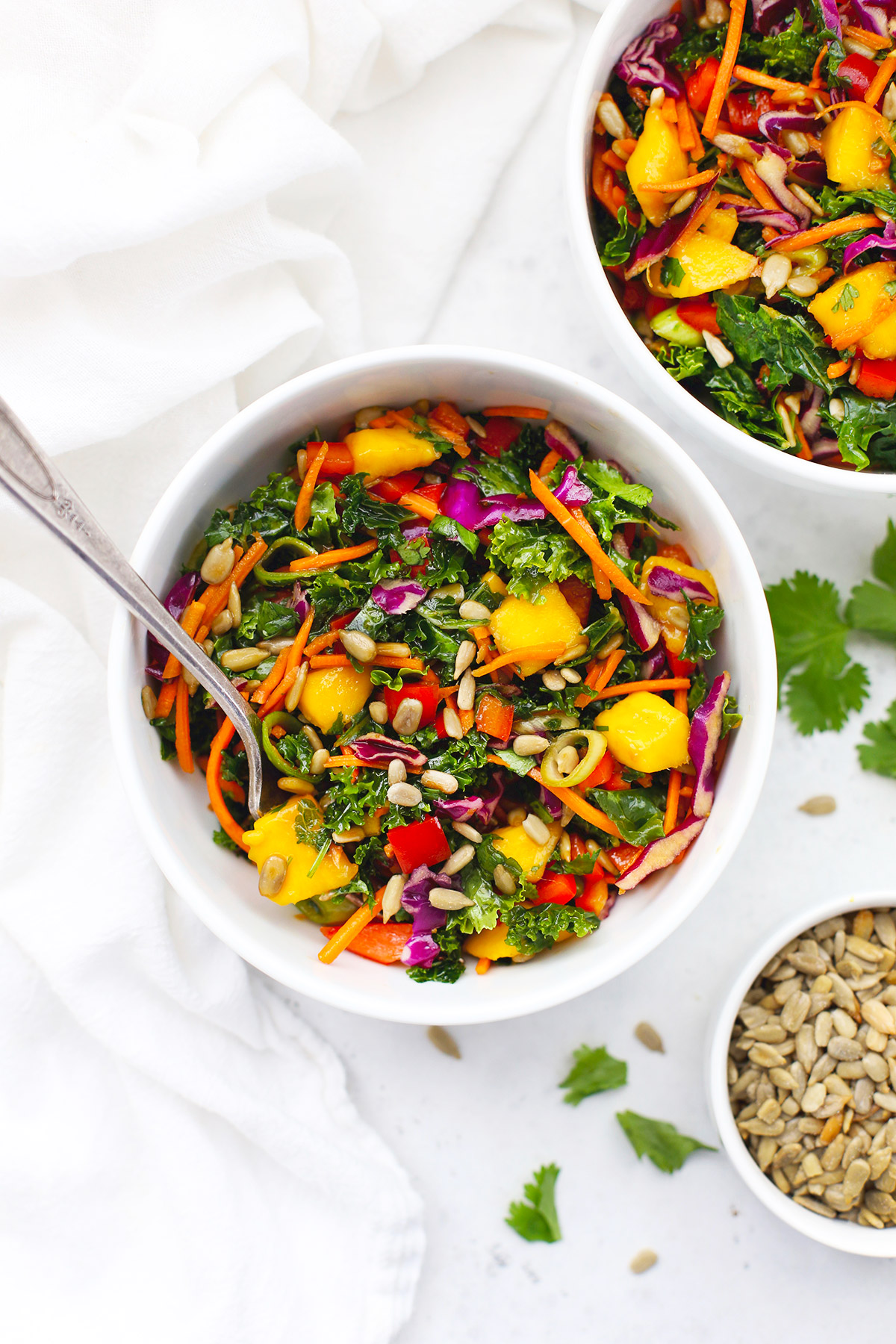 Two bowls of Asian Kale Crunch Salad in white bowls on a white background