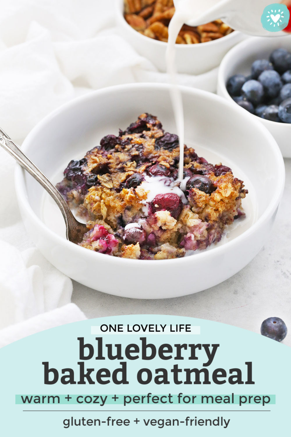 "Pouring almond milk over a bowl of blueberry baked oatmeal with text overlay that reads ""One Lovely Life Blueberry Baked Oatmeal. Warm + cozy + perfect for meal prep. Gluten-free + vegan-friendly"""