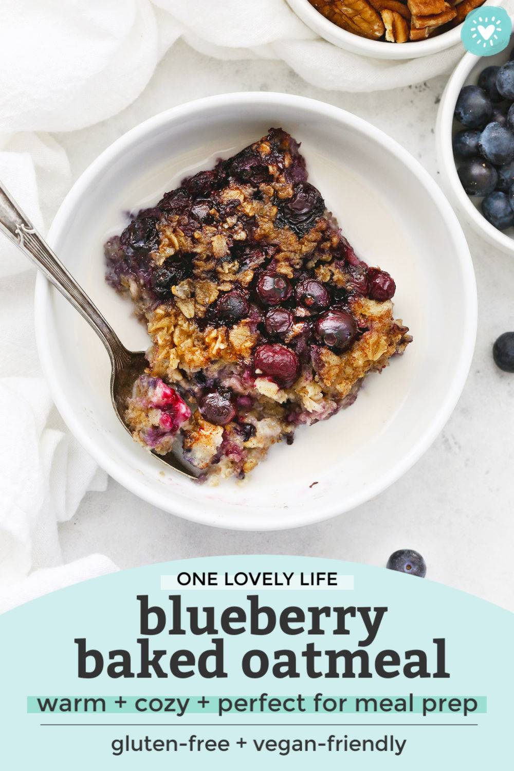 "Overhead view of a bowl of blueberry baked oatmeal with almond milk on a white background with text overlay that reads ""One Lovely Life Blueberry Baked Oatmeal. Warm + cozy + perfect for meal prep. Gluten-free + vegan-friendly"""