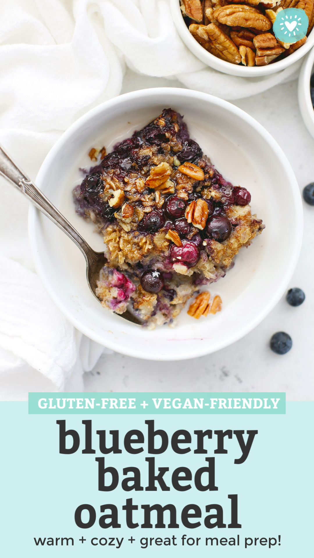 "Overhead view of a bowl of blueberry baked oatmeal with almond milk on a white background with text overlay that reads ""Gluten-Free + Vegan-Friendly Blueberry Baked Oatmeal. Warm + Cozy + Great for Meal Prep!"""