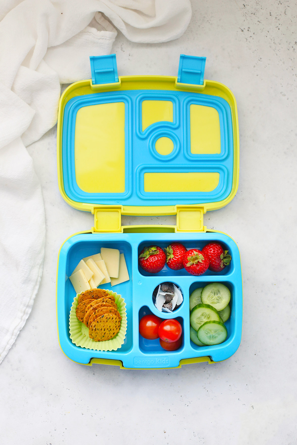 Blue and Yellow Bentgo lunchbox with cheese, crackers, strawberries, tomatoes, cucumbers, and trail mix.