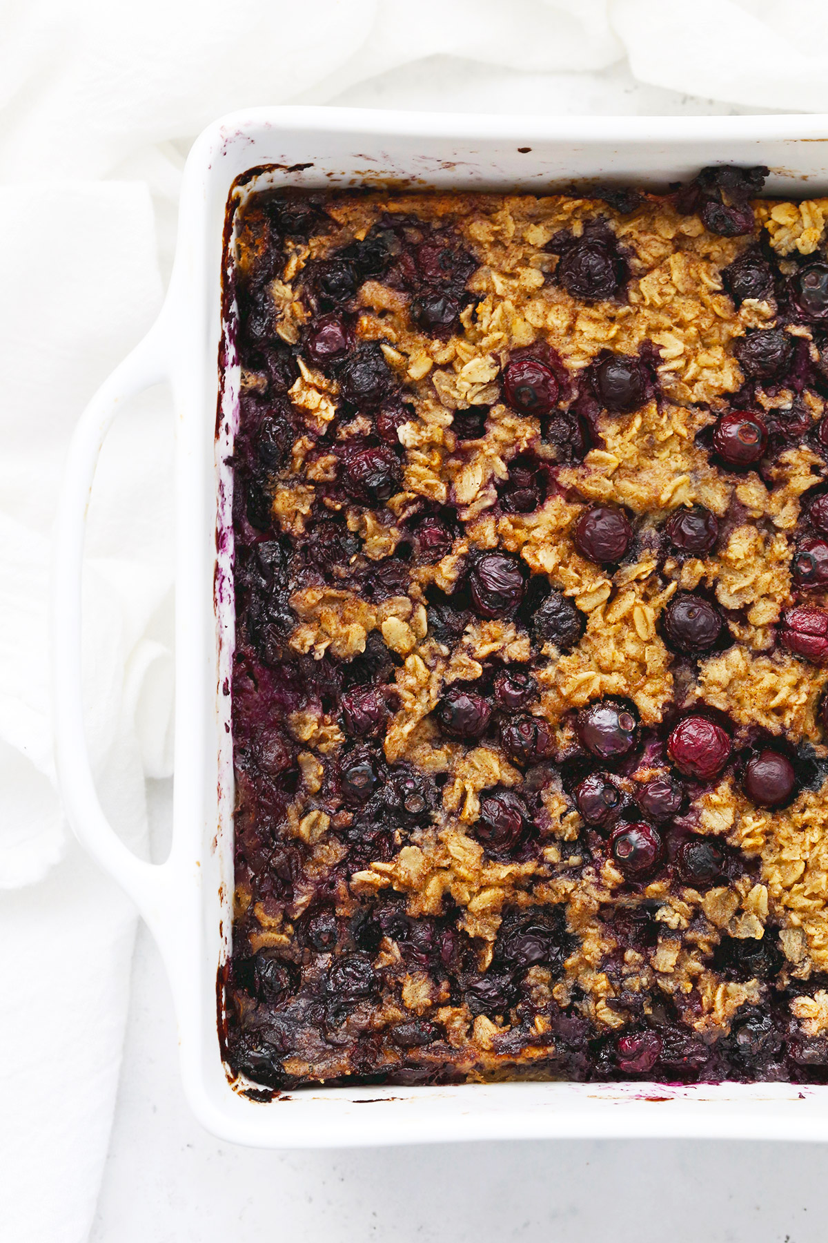 Closeup view of A white baking dish of blueberry baked oatmeal on a white background