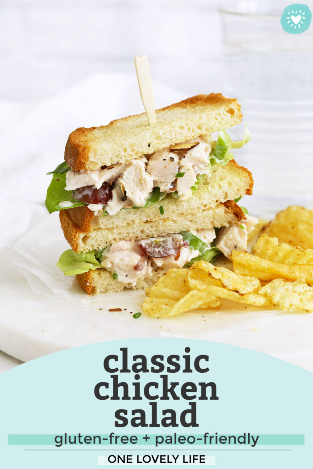 "A gluten-free chicken salad sandwich on a marble serving board with kettle chips next to it with text overlay that reads ""Classic Chicken Salad. Gluten-Free + Paleo-Friendly. One Lovely Life"""